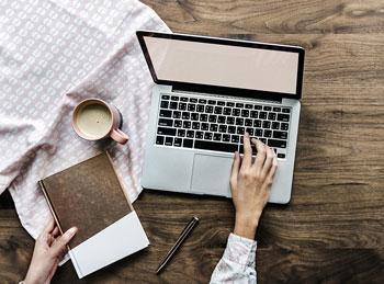 Bloger przepisujący treść z notatnika do bloga