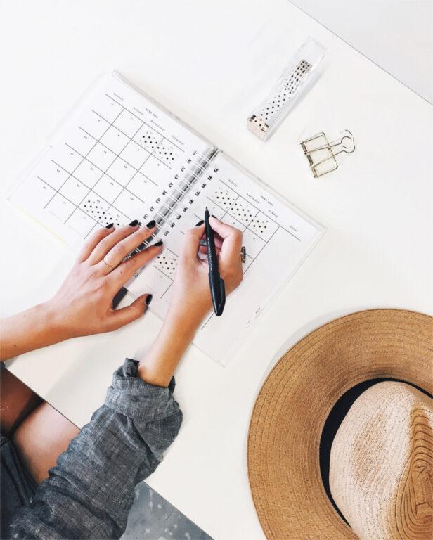Na biurku leży kalendarz i kapelusz, kobieta robi notatki