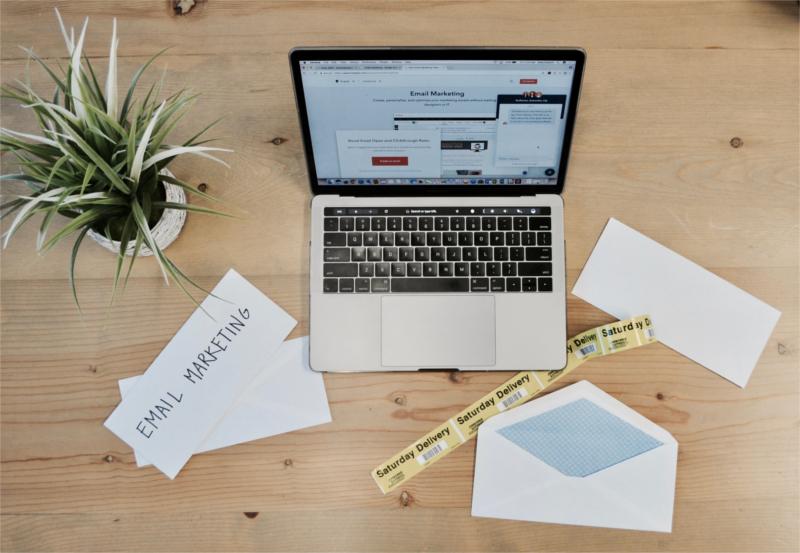 Komputer,  koperta i kartka z napisem E-mail marketing na biurku