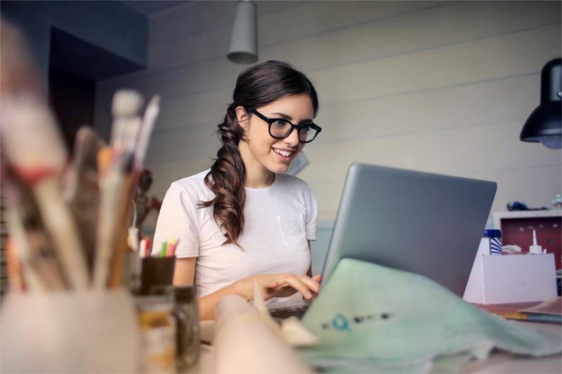Entuzjastyczna kobieta siedzi przy biurku i komputerze, pisze