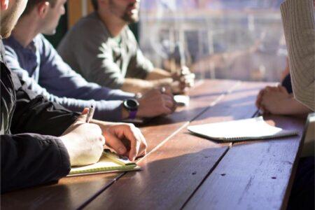 Przy stole siedzą ludzie którzy robią notatki na papierze