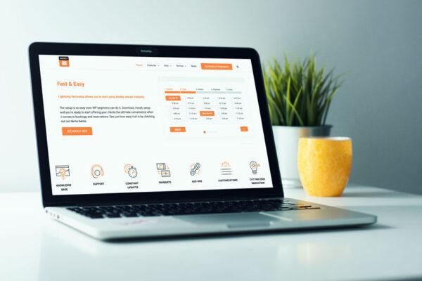 Laptop z zanstalowaną wtyczką kalendarza online na biurku, na tle rośliny