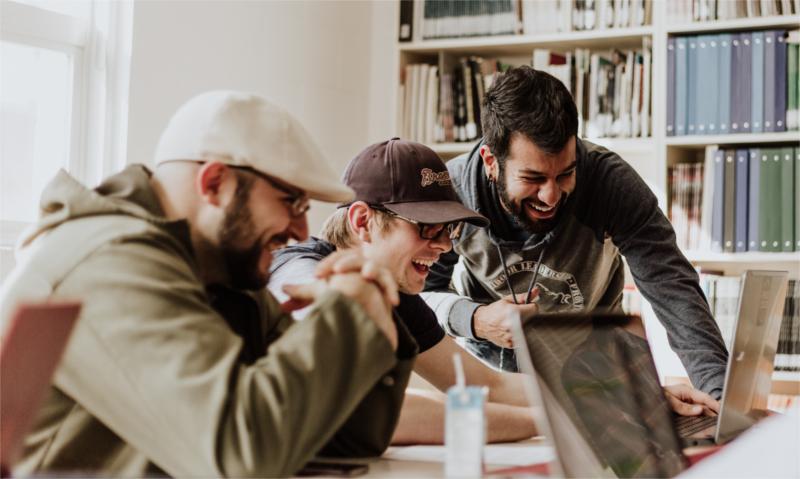 Trzech mężczyzn z ogromnym entuzjazmem patrzy w monitor laptopa