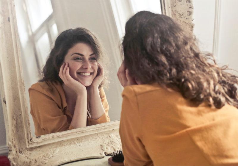 Kobieta uśmiecha się do siebie w lustrze w ramach terapii w renomowanym gabinecie psychoterapeutycznym