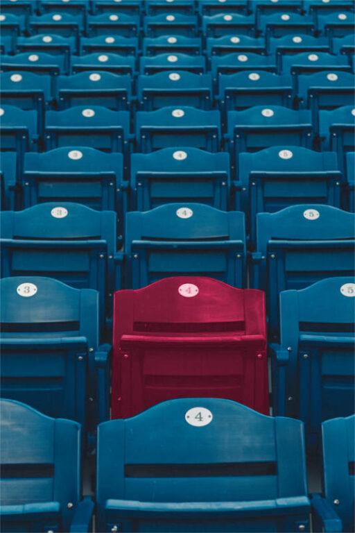Mnogość rzędów identycznych foteli - z wyjątkiem jednego - o odmiennym kolorze, symbolizują możliwość wyróżnienia się spośród tysięcy podobnych usług na rynku, możesz to osiągnąć jeśli zastosujesz hashtagi w marketingu gabinetu.