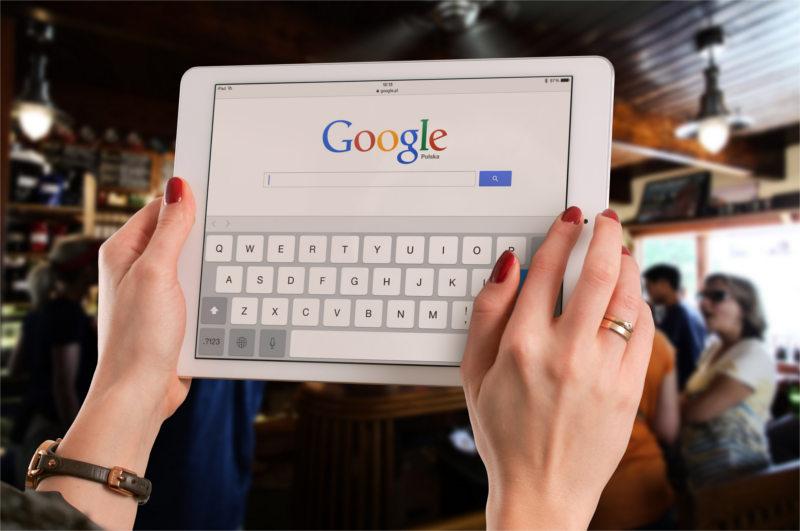 Tablet w rękach kobiety psychologa - na tablecie reklama gabinetu w Google Ads